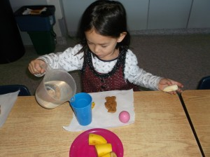 A YMCA Childcare participant prepares her snack