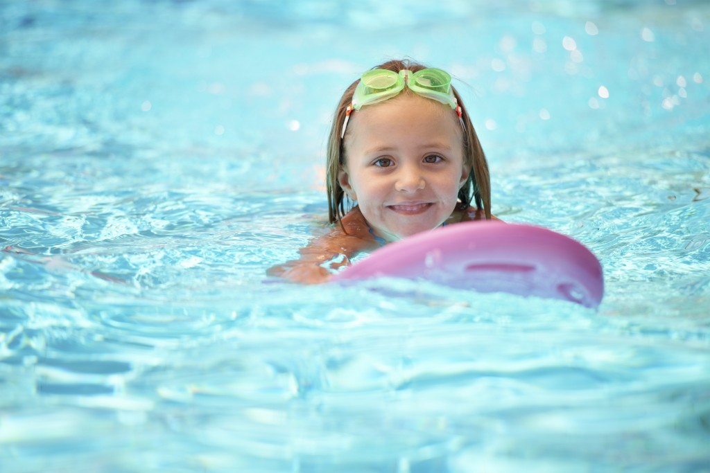 A cute little girl using a flotation device while swimming