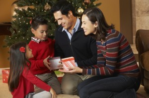 Family Opening Presents In Front Of Christmas Tree