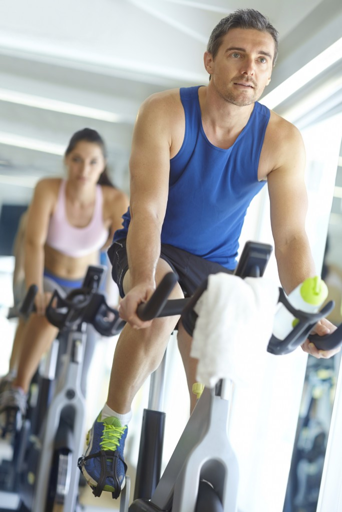 A man and woman exercising in spinning class at the gym