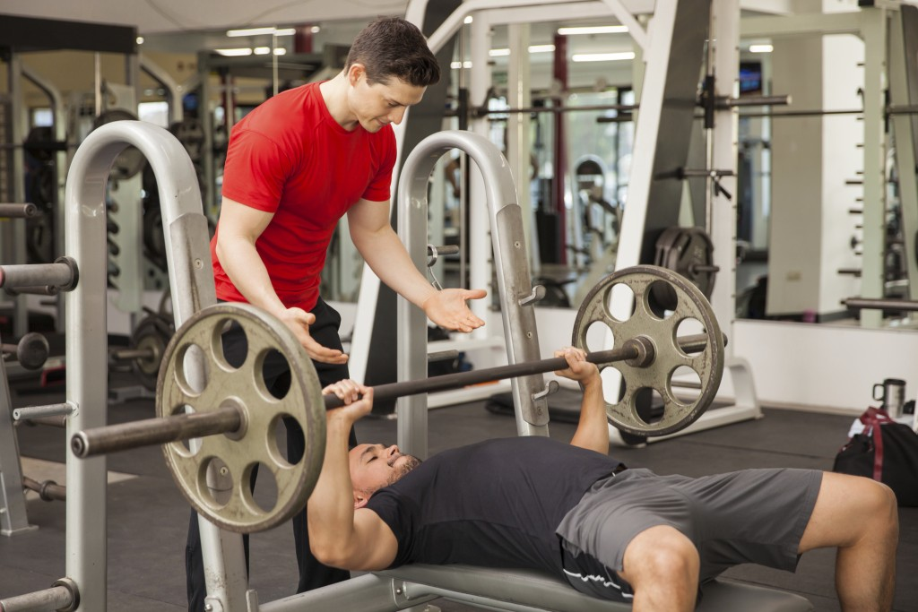 Strong young man spotting another guy while he lifts a barbell at a gym