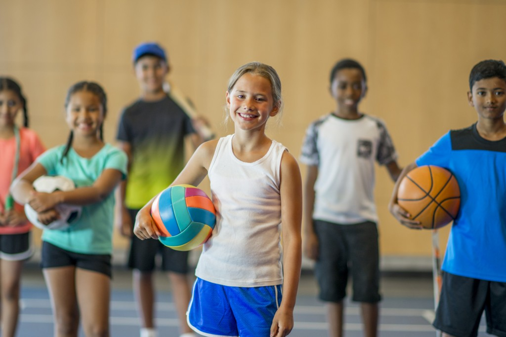 A multi-ethnic group of elementary age children are playing various sports together at the gym. They are smiling and looking at the camera.