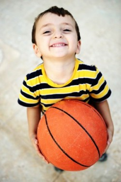 Boy with bball looking up happy